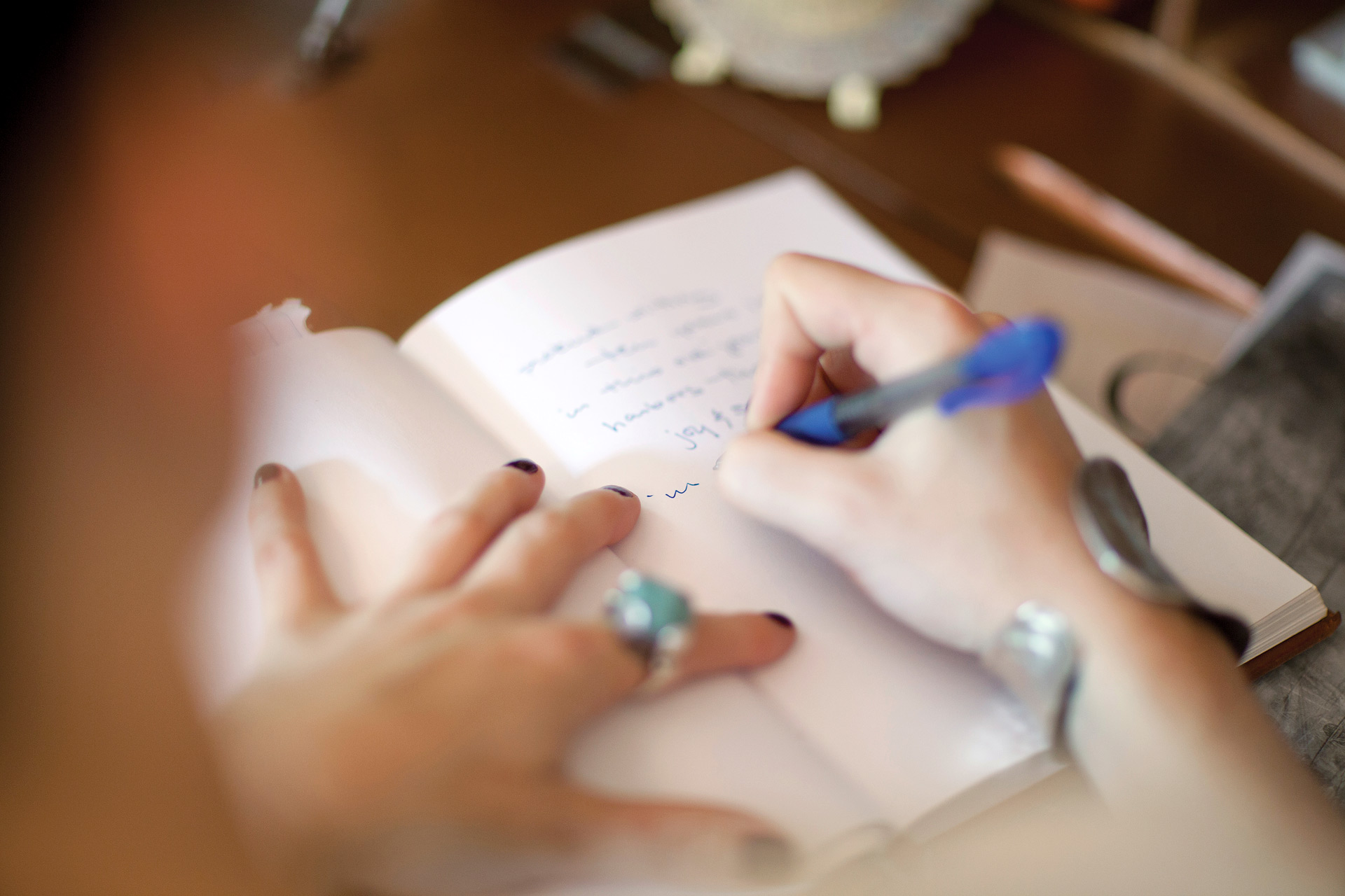 Creative writing student putting pen to paper