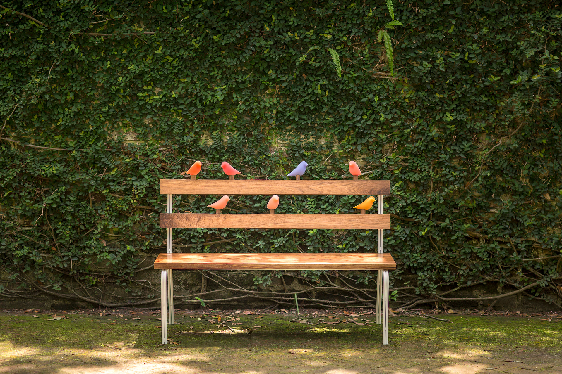A wooden bench with bird shaped interactive components