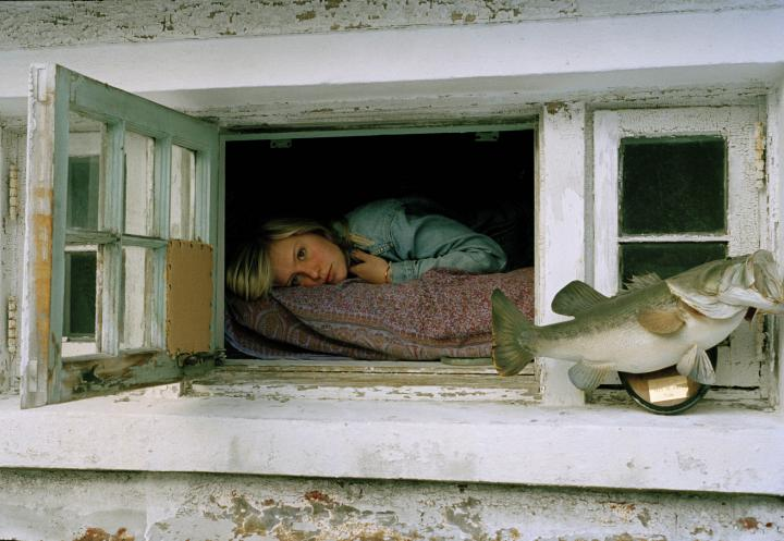 A girl lying on a bed looking out an open window with a mounted bass on the sill