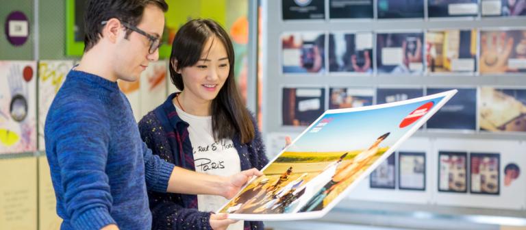 Advertising students looking at print designs