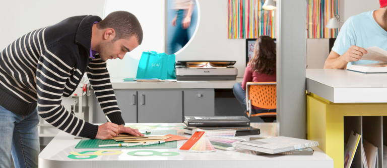 Graphic design student using cutting mat in Adler Hall