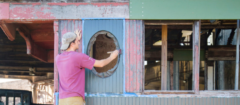 Preservation design students painting train car