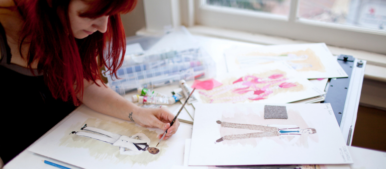 Production design student using watercolors to create costume designs