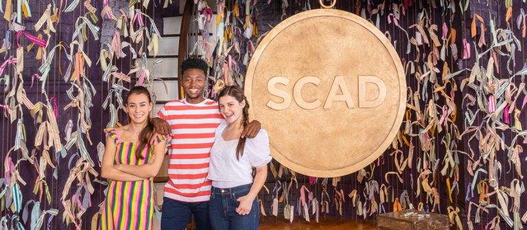SCAD students in Poetter Hall stand next to a large SCAD medallion.