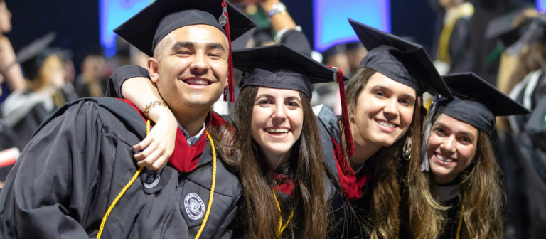 Four graduates holding diplomas and wearing cap and gown smile