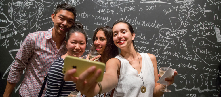 Group of people smiling and taking a selfie