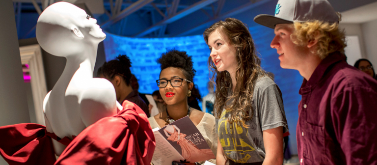 SCAD Atlanta students admiring garment at SCAD FASH reception