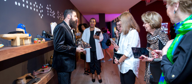 Visitors attending SCAD FASH Shoes exhibition reception