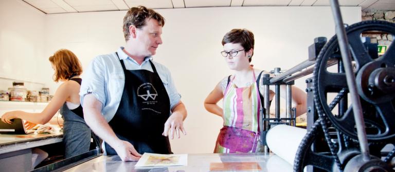 Printmaking professor instructing student at printing press