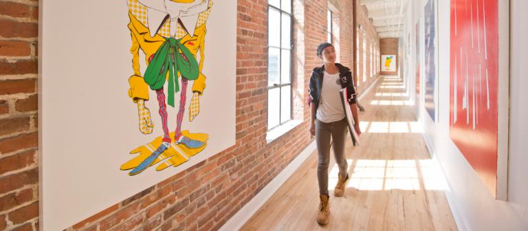 Alexander Hall, SCAD Savannah walks in long hallway while looking at hanging artwork