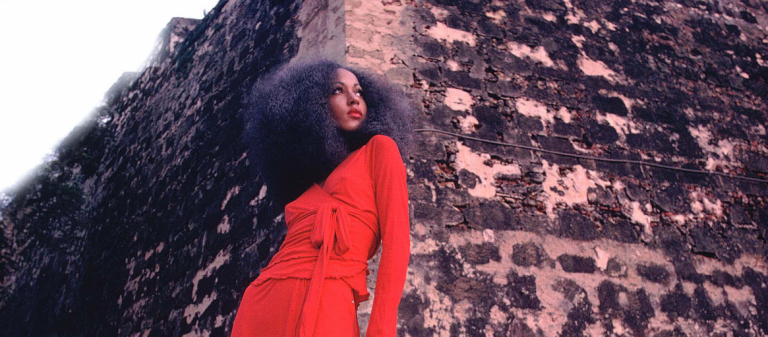 Pat Cleveland in red two-piece matte jersey skirt with wrap top and matching red stockings and shoes