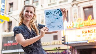 Emilie Kefalas holding Replay poster