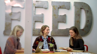 Lauren Bush Lauren sits with two others at a work table