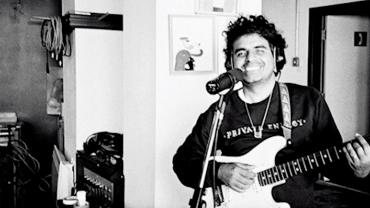 Musician Robert Carlos Lange, also known as Helado Negro, plays guitar in a studio.