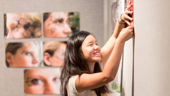 Summer programs student hanging photography prints for critique