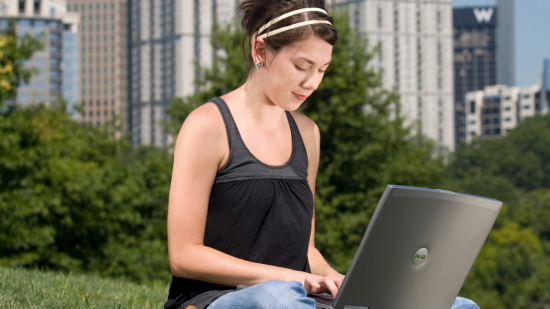 online student using laptop outside in city park
