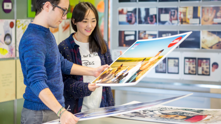 Advertising students looking at print designs