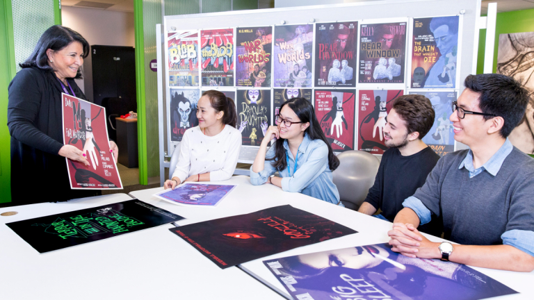 SCAD professor of advertising showing movie posters to students