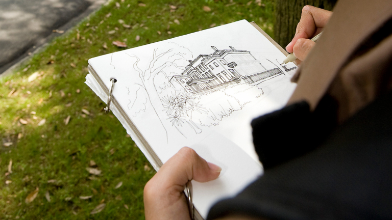 Architectural history student drawing building on sketchpad