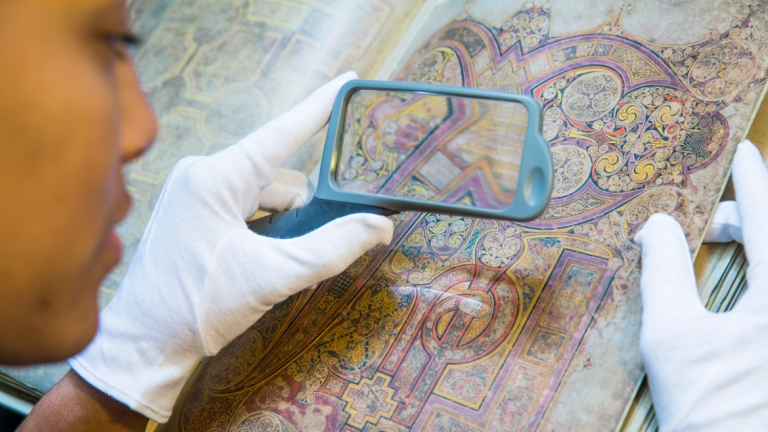 Art history student using magnifying glass
