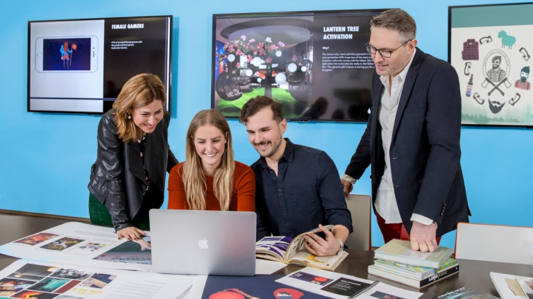 Branded entertainment students collaborating at table with computer