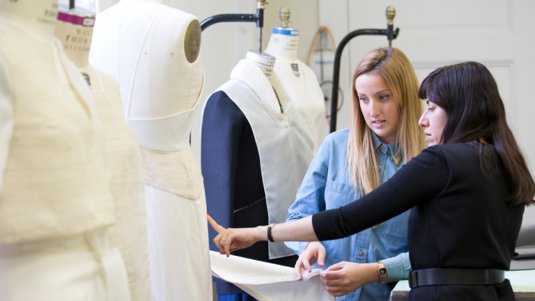 Fashion mentor Benhaz Sarafpour critiquing garment with student