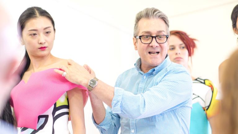 Fashion professor critiquing student garment on model