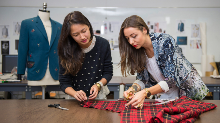 Fashion professor measuring and cutting fabric with student