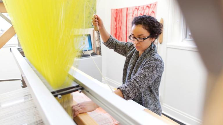 Fibers student weaving on Jacquard loom