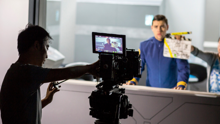 Film and television students syncing shot with clapperboard