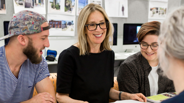 Graphic design students collaborate with a professor in the classroom