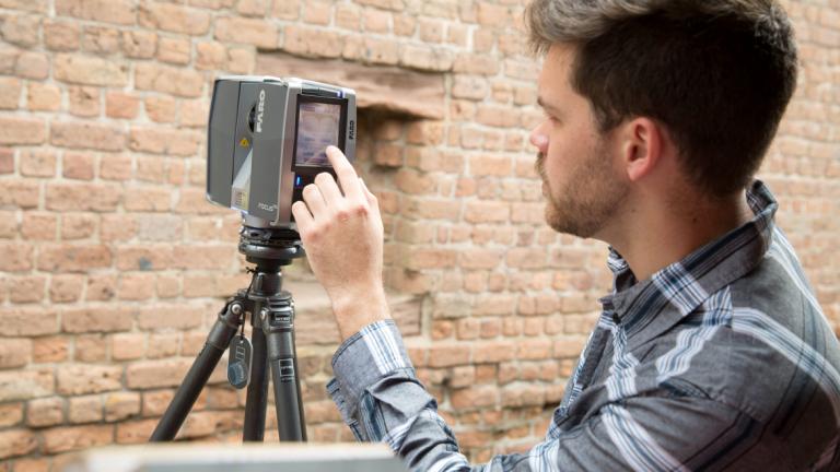 Preservation design student using 3D scanner to survey