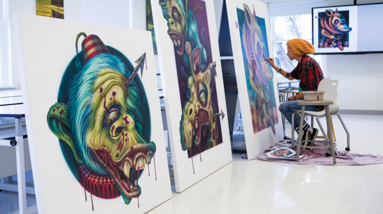 Illustration student painting on large canvas in Haymans Hall