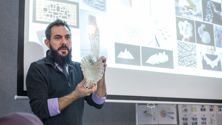 Industrial design professor presenting 3D model in classroom lecture