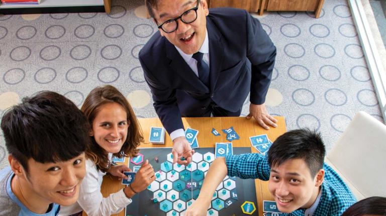 Interactive design and game development professor and students explore a board game