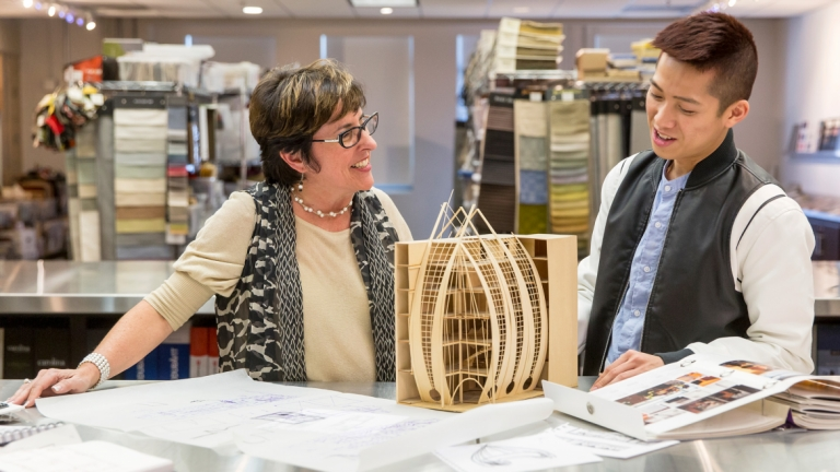 Interior design professor looking at building model with student