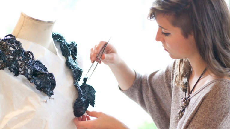 Jewelry student crafting a design on mannequin