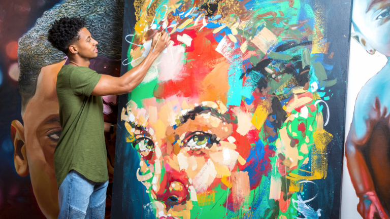 SCAD alumnus Jon Moody painting a canvas