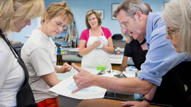 Educator programs participants with printmaking professor