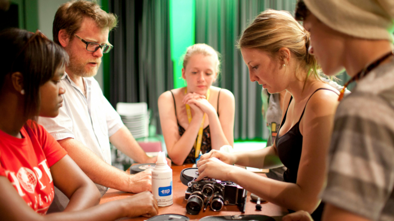 Rising Star students learning about camera with professor