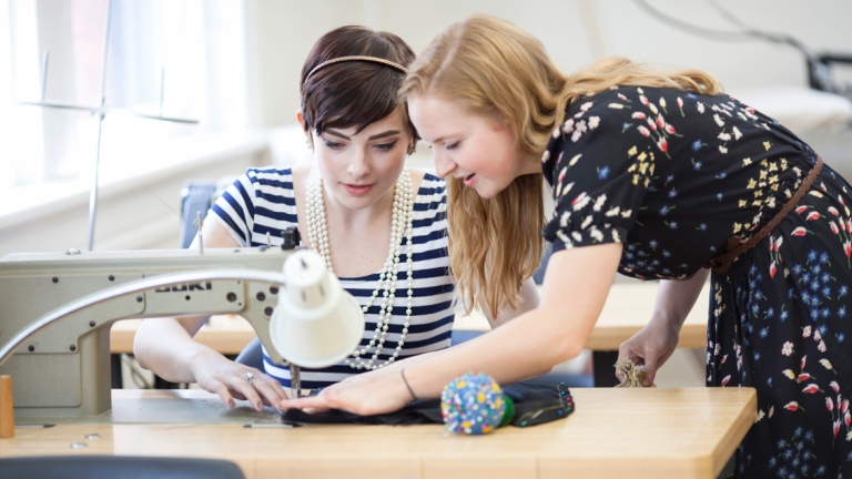 Rising Star students working on sewing machine in classroom