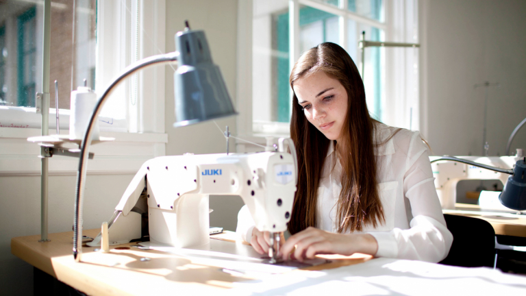Fashion student learning sewing skills in Eckburg Hall