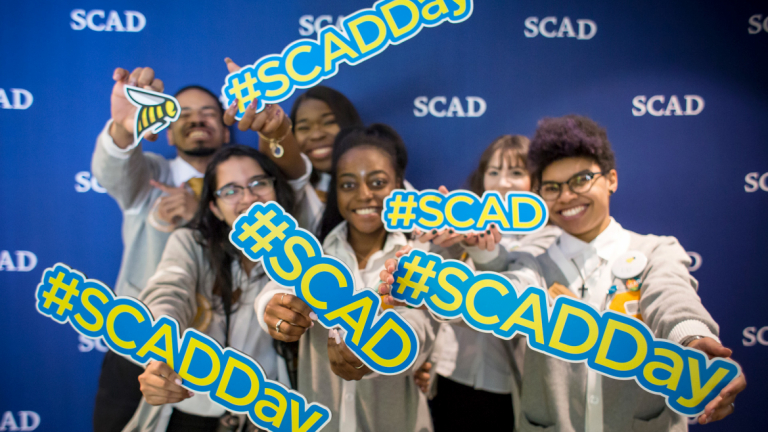 Exuberant students hold #SCAD signs