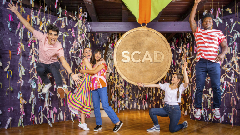 SCAD students celebrate in Poetter Hall next to large SCAD medallion.