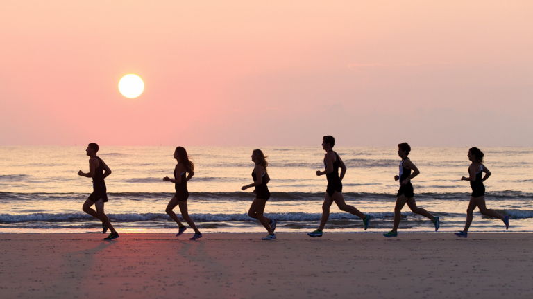 SCAD cross country athletes run across beach at sunset