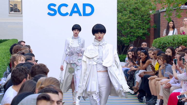 Two models walk down SCAD runway wearing white and sporting bowl cuts
