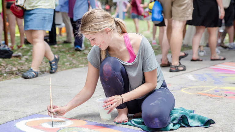 Young woman uses a paint brush to create her sidewalk chalk masterpiece