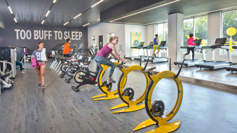 Student works out on brightly colored stationary yellow bike in modern gym setting