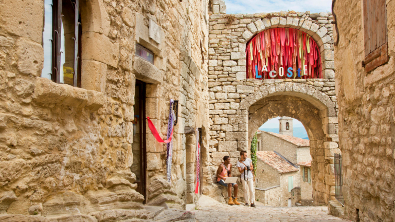 Students have a conversation in the cobbled streets of Lacoste, France