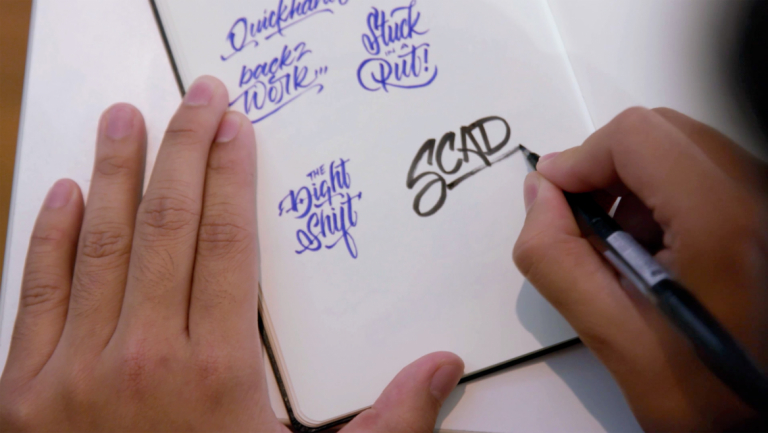 hand writing SCAD in a notebook